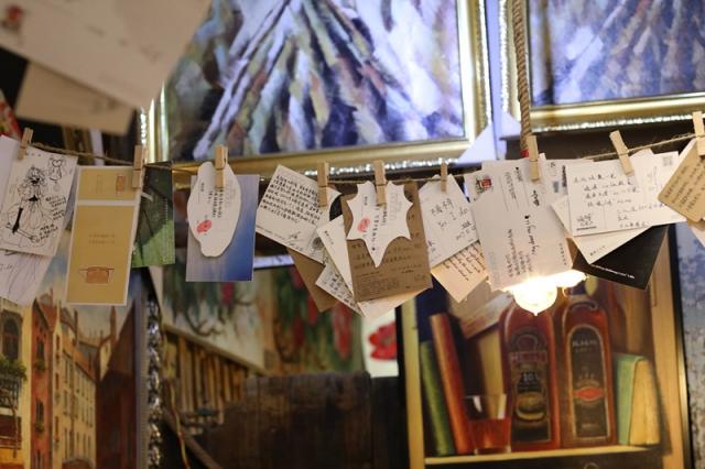 """""""乐艺活""""不仅是一间咖啡店,同时还是一间油画廊,这个名字来源于英文life is art 2(to)us,——生活对我们来说就是艺术。在这个狭小的空间里,里面的装饰,都是他自己手工制作的,充满了东南亚风情小木屋式的感觉。不仅挂满了各式各样的油画,还挂满了许多的明信片,上面都是客人,或路人留下的话,有致未来的自己,有纪念过去的种种,还有留给心里的人……"""