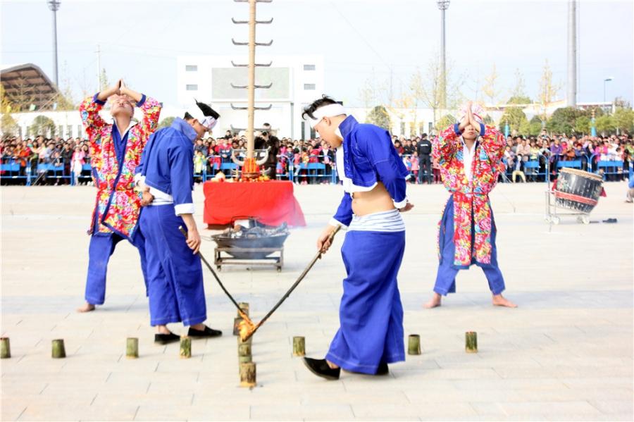 瑶族阿哥在给地上的竹筒点火,一会儿下火海的表演者将赤脚从竹筒上走过。