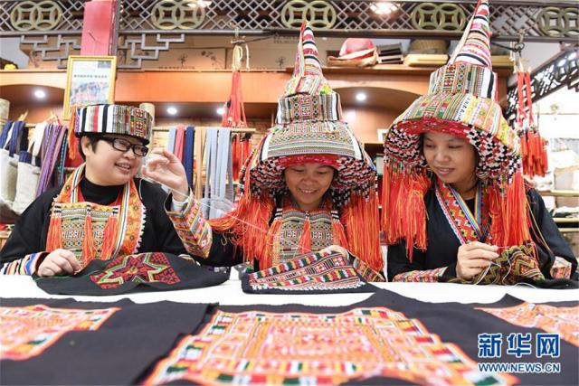 """12月5日,在广西贺州市八步区一家瑶族服饰刺绣艺术馆,三名绣娘在加工瑶族服饰产品。广西贺州市瑶族服饰具有鲜明的地域特征,2006年被列入第一批国家级非物质文化遗产名录。近年来,当地瑶族服饰技艺传承人根据市场需求,不断创新开发服饰产品,让这一古老""""非遗""""在市场中闯开新路。目前,贺州市瑶族服饰开发创新产品超过100种,产品受到消费者的广泛欢迎,并带动了各县区超过600名""""绣娘""""依靠针线活在家里就业增收。新华社记者 陆波岸 摄"""