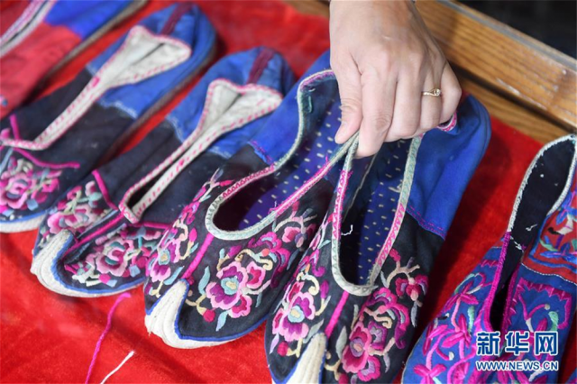 """12月5日,在广西贺州市八步区一家瑶族服饰刺绣艺术馆,一名女子在整理瑶族鞋子。广西贺州市瑶族服饰具有鲜明的地域特征,2006年被列入第一批国家级非物质文化遗产名录。近年来,当地瑶族服饰技艺传承人根据市场需求,不断创新开发服饰产品,让这一古老""""非遗""""在市场中闯开新路。目前,贺州市瑶族服饰开发创新产品超过100种,产品受到消费者的广泛欢迎,并带动了各县区超过600名""""绣娘""""依靠针线活在家里就业增收。新华社记者 陆波岸 摄"""