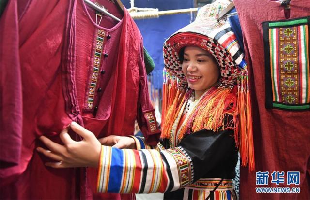 """12月5日,在广西贺州市八步区一家瑶族服饰刺绣艺术馆,一名女子在整理瑶族服装。广西贺州市瑶族服饰具有鲜明的地域特征,2006年被列入第一批国家级非物质文化遗产名录。近年来,当地瑶族服饰技艺传承人根据市场需求,不断创新开发服饰产品,让这一古老""""非遗""""在市场中闯开新路。目前,贺州市瑶族服饰开发创新产品超过100种,产品受到消费者的广泛欢迎,并带动了各县区超过600名""""绣娘""""依靠针线活在家里就业增收。新华社记者 陆波岸 摄"""