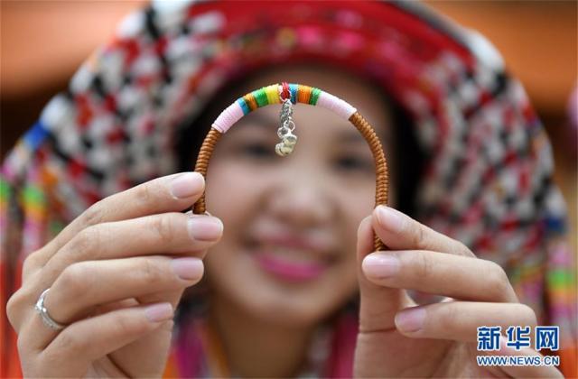 """12月5日,在广西贺州市八步区一家瑶族服饰刺绣艺术馆,一名女子在展示瑶族饰品。广西贺州市瑶族服饰具有鲜明的地域特征,2006年被列入第一批国家级非物质文化遗产名录。近年来,当地瑶族服饰技艺传承人根据市场需求,不断创新开发服饰产品,让这一古老""""非遗""""在市场中闯开新路。目前,贺州市瑶族服饰开发创新产品超过100种,产品受到消费者的广泛欢迎,并带动了各县区超过600名""""绣娘""""依靠针线活在家里就业增收。新华社记者 陆波岸 摄"""
